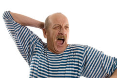 Elderly  man in a stripped vest yawns Royalty Free Stock Photos
