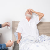 Elderly man with strong headache while sitting in bed Stock Photo