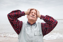 Elderly man suffering from a headache on sea background Royalty Free Stock Photo