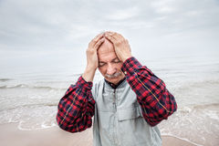 Elderly man suffering from a headache on sea background Royalty Free Stock Photography