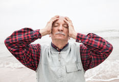 Elderly man suffering from a headache on sea background stock photos
