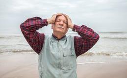 Elderly man suffering from a headache on sea backg Stock Photo