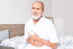 Elderly man suffering from stomachache. Elderly man sitting on bed suffering from stomach problems Royalty Free Stock Image