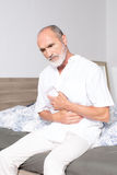 Elderly man suffering from stomachache. Elderly man sitting on bed suffering from stomach problems Royalty Free Stock Photos