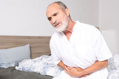 Elderly man suffering from stomachache. Elderly man sitting on bed suffering from stomach problems Stock Images