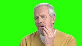 Elderly man suffering from toothache. Senior man with terrible toothache on chroma key background. Medicine and dentistry concept stock footage
