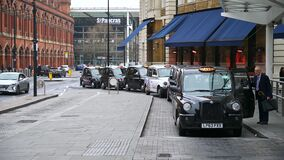 An elderly man in a suit gets into a waiting black London taxi cab outside King`s Cross St. Pancras Railway Station as younger