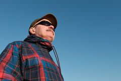 An elderly man in sunglasses and a baseball cap looks away. stock photography