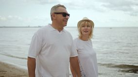 Elderly man in sunglasses holding hand of mature female pensioner. stock footage