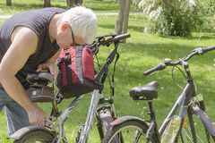 An elderly man in sunglasses repairing a bike in the Park royalty free stock image