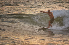 Elderly man surfing on the golden waves. At Hikkaduwa, Sri Lanka royalty free stock image