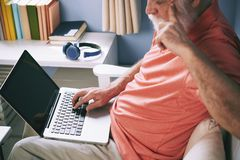 Elderly man surfing the net. Elderly man holding laptop on his lap and surfing the net at home Stock Photos