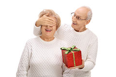 Elderly man surprising an elderly woman with a gift Stock Photography