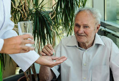 Elderly man takes medication Stock Images