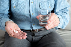 Elderly man taking medicament. And holding glass of water Royalty Free Stock Images