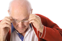 Elderly man taking off his glasses. Isolated on white Royalty Free Stock Photo