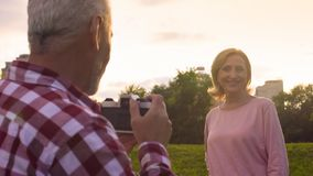 Elderly man taking photos of his attractive wife in park at sunset, date, hobby stock image