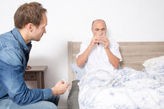 Elderly man taking a pill while sitting in bed Stock Photo