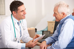 Elderly man talking with an American doctor Stock Photography