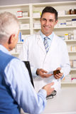 Elderly man talking with American pharmacist Stock Photo