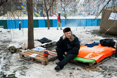 Elderly man talking on a cell phone. KIEV, UKRAINE: Elderly man talking on a cell phone while sitting on winter street during Euromaidan protest. More than 800 Royalty Free Stock Photography