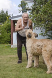 Elderly man talking with a dog Stock Photo