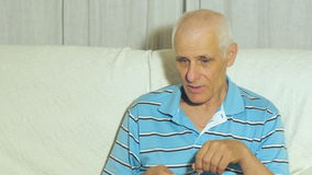 Elderly man talks. Aged gray-haired male complains holding eyeglasses in hand sitting on sofa at home stock video