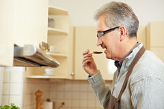 Elderly man tasting soup Royalty Free Stock Photography