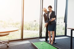 An elderly man is teaching his secretary to play mini golf. He directs her Stock Image