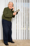 Elderly man on telephone holding picture frame Royalty Free Stock Photos