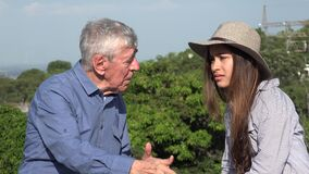 Elderly man telling story to teen girl. A grandfather and a granddaughter