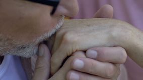 Elderly man tenderly kissing hand of beloved old woman, couple in love, close up stock footage
