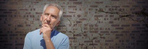 Elderly man thinking against brown brick wall. Digital composite of Elderly man thinking against brown brick wall Royalty Free Stock Images