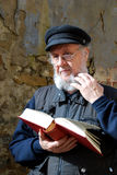 Elderly man thinking about the book Royalty Free Stock Photography