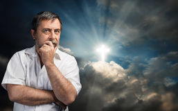Elderly man thinking about faith and God. Religious conversion concept. Elderly man thinking about faith and God. Portrait against the sky with a glowing cross Royalty Free Stock Image