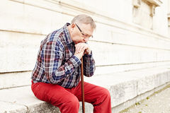 Elderly man thinking outdoor closeup. Close-up portrait of pensive mature man in glasses and plaid shirt resting leaning on his wooden walking stick Stock Image
