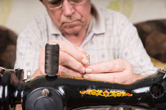 Elderly man threading a needle with yarn Stock Photo