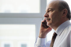 Elderly man in a tie carefully listen to the interlocutor on the. Holding phone and listen carefully to speaker Royalty Free Stock Photography
