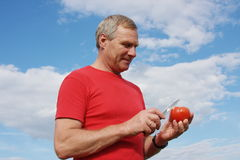 Elderly man with a tomato in a hand. On a background blue sky Stock Photography