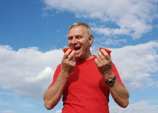 Elderly man with a tomato in a hand. On a background blue sky Royalty Free Stock Photos