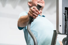 Elderly man training on cross trainer at the gym Stock Image