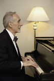 Elderly man in tuxedo playing piano Stock Images