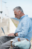 Elderly man typing on laptop and listening music in earpods outdoors Royalty Free Stock Images