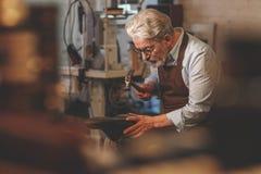 An elderly man in uniform. In a workshop stock image