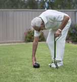 Elderly Man Using Artificial Bowling Arm. An elderly man uses a bowling arm to lean on as he bends over to adjust the bowling ball on the lawn Stock Photography