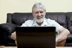 Elderly man using computer. Elderly man in front of a laptop stock photo