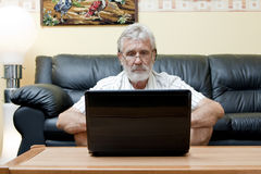 Elderly man using computer. Elderly man in front of a laptop Stock Photo