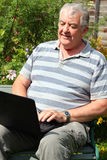 Elderly man using a laptop in a garden. Stock Images