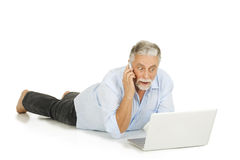 Elderly man using laptop and mobile Stock Image