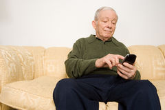 Elderly man using remote control Stock Image